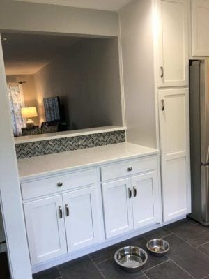 A kitchen remodeled including a new window from kitchen to living room, granite bar top, cabinets, vanity, backsplash tile, and floor tile.