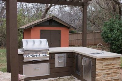 Outdoor kitchen remodeled with new concrete, new counters, new cabinets, new sink, new stone facing, and new pergola.